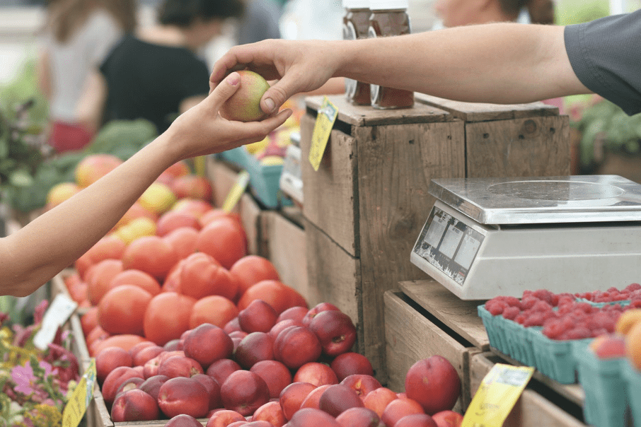 Kobieta kupuje jabłko na lokalnym targowisku.